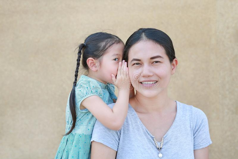 Cute little Asian child girl whispering a secret to her young mothers ear at home. Family and relationships concept royalty free stock photo