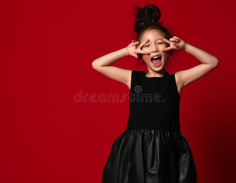 Cute little asian girl ballerina in beautiful black dress is dancing showing peace sign on red. Background royalty free stock photography
