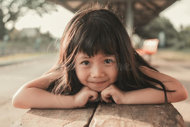 Cute Little Asian Girl. Close up Asian Thai Girl Smile In a Comfortable on Wooden Chair stock images