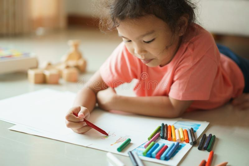 Cute little asian girl drawing homework and writing with color Wax crayons on paper in her home royalty free stock photos