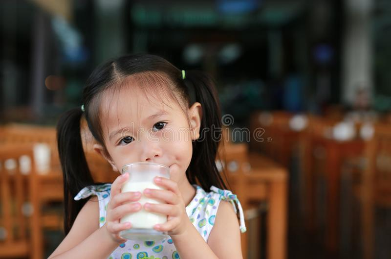 Cute Little asian girl drinking glass of fresh milk in coffee shop stock photography