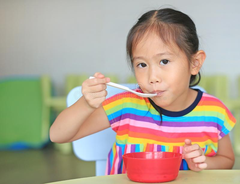 Cute little Asian girl eating cereal with cornflakes and milk on the table. Children having breakfast at morning royalty free stock image