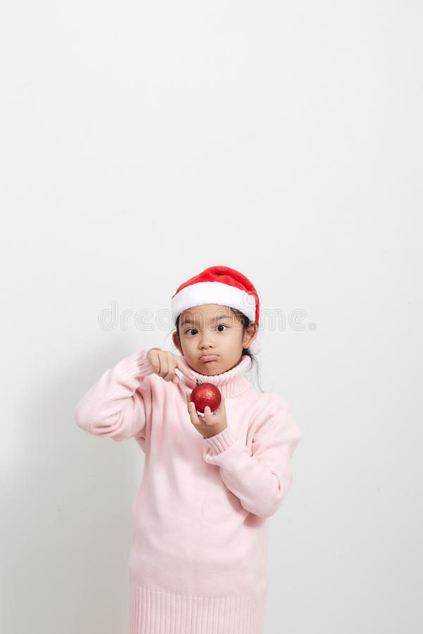 Girl holding a red christmas ball in sweater and santa hat royalty free stock images