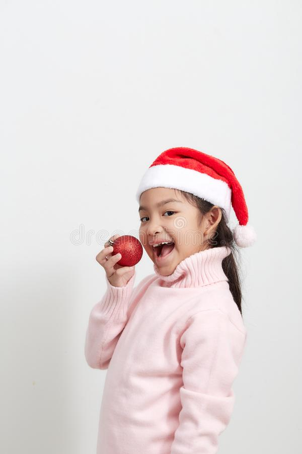 Girl holding a red christmas ball in sweater and santa hat stock image
