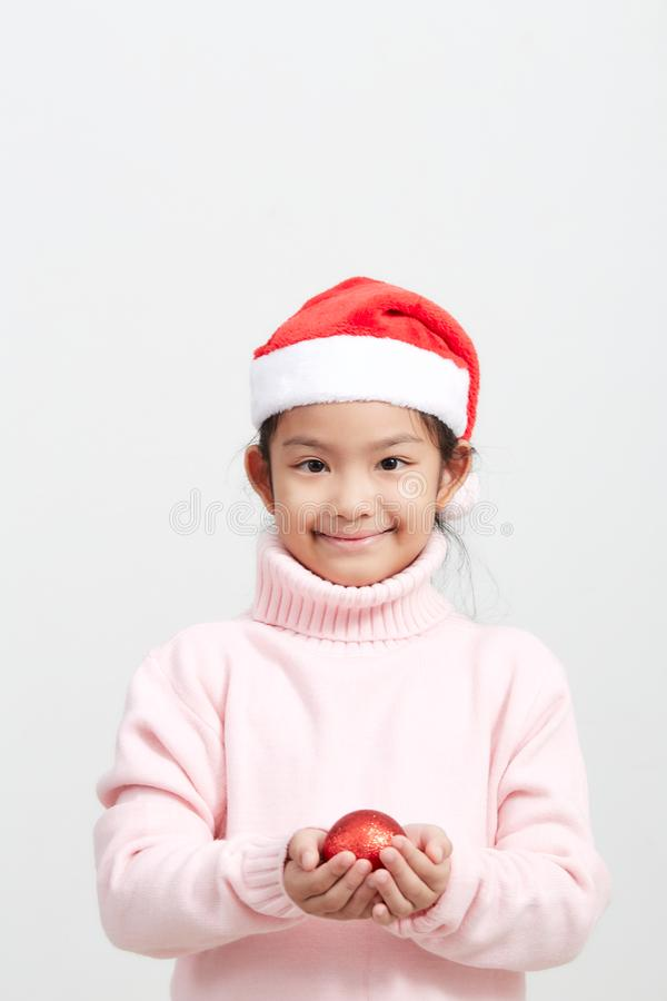 Girl holding a red christmas ball in sweater and santa hat stock photos