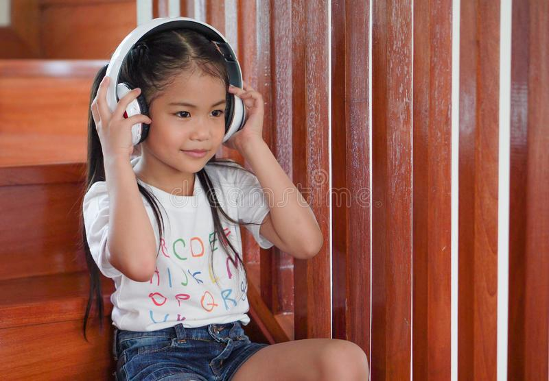 Cute little asian girl listening music with headphones on stairs at home stock photo