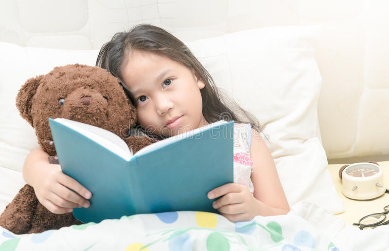 Cute little asian girl in nightdress reading a book with teddy b stock photography