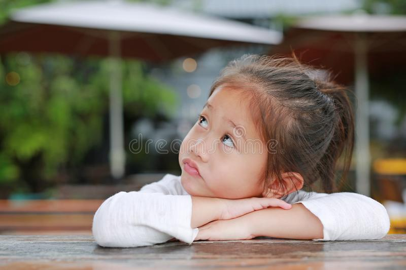 Cute little Asian kid girl with funny face lying on the wooden table with looking up royalty free stock images