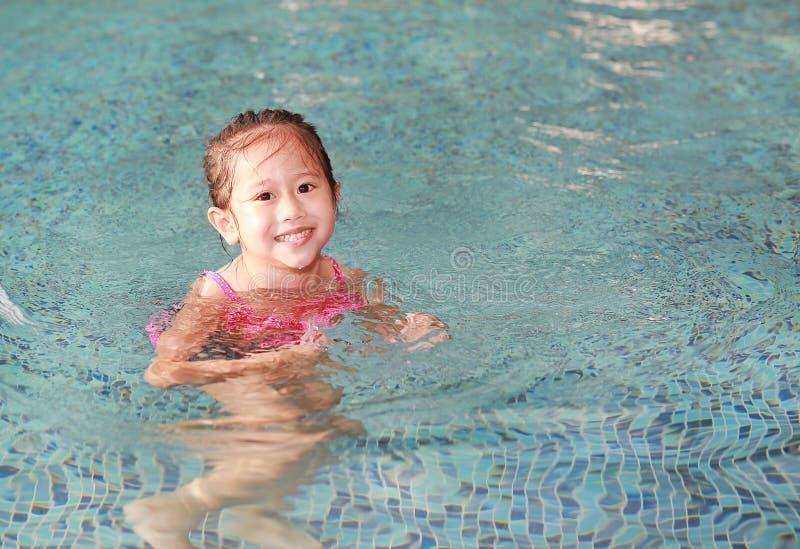 Cute little Asian kid girl has fun playing in the pool.  royalty free stock photo