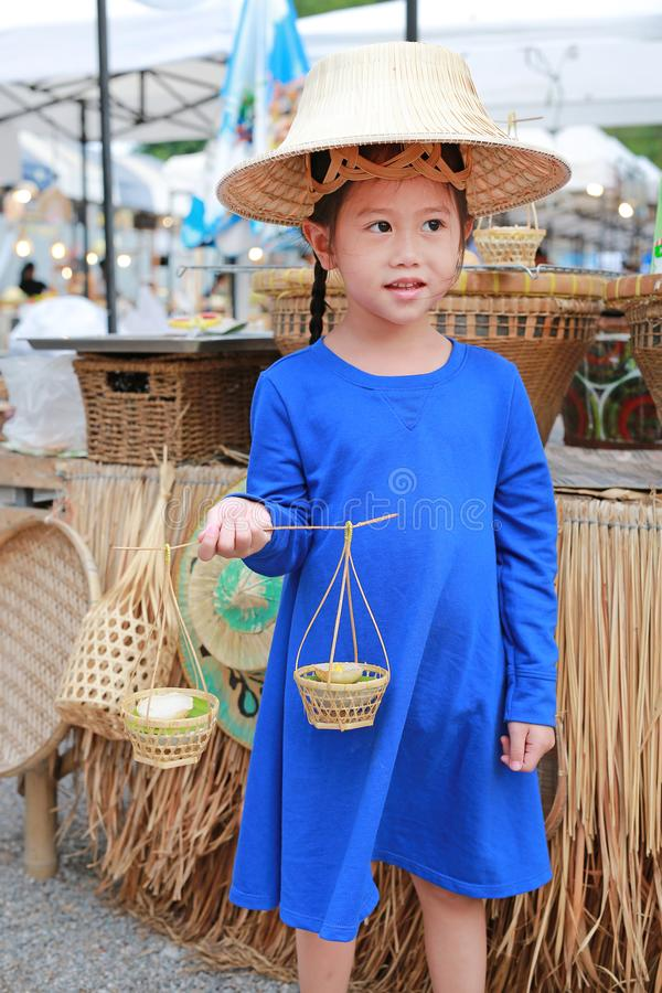 Cute little Asian kid girl wearing farmer hat with holding thai style candy in hand royalty free stock photography