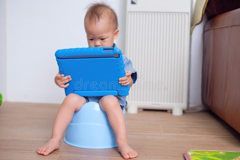 Cute little Asian 18 months / 1 year old toddler baby boy child is on blue potty while playing with digital tablet at home stock photography