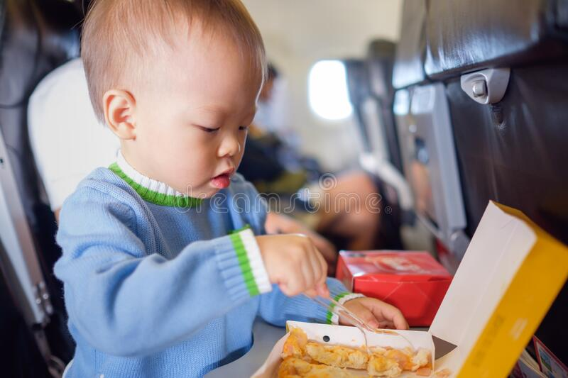 Cute little Asian 18 months / 1 year old toddler baby boy child wearing blue sweater eating food during flight on airplane stock images