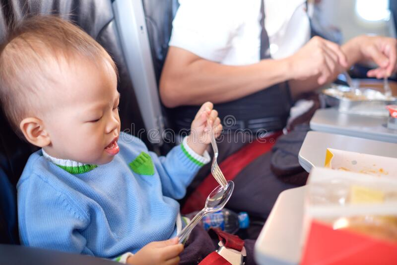 Cute little Asian 18 months / 1 year old toddler baby boy child wearing blue sweater eating food during flight on airplane. Flying stock photography