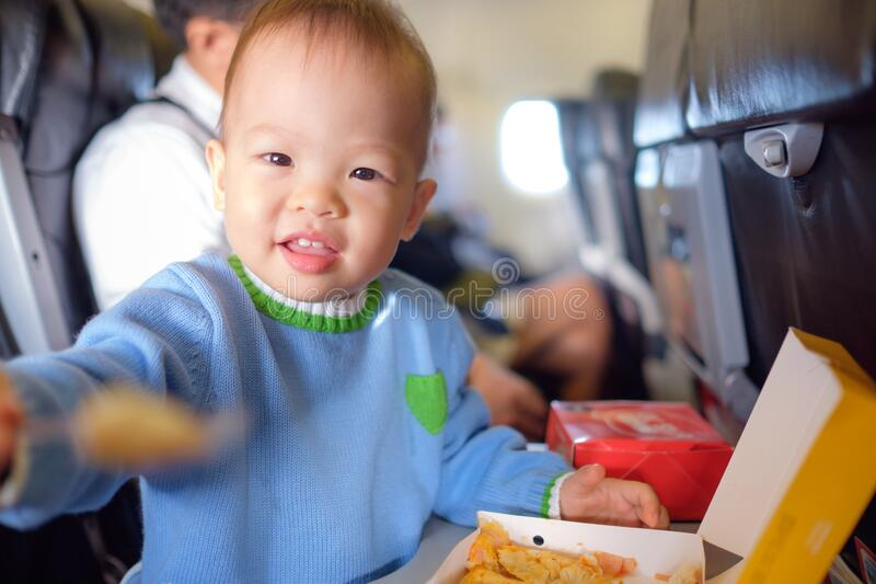 Cute little Asian 18 months / 1 year old toddler baby boy child wearing blue sweater eating food during flight on airplane stock photography