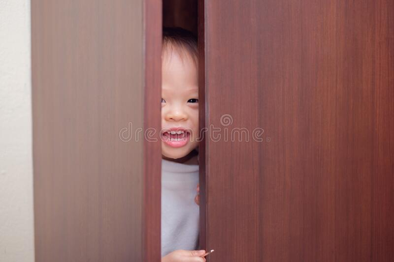 Cute little Asian 18 months / 1 year old toddler baby boy child wearing white sweater is hiding in the closet at home stock images