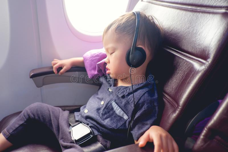 Toddler boy sitting with safety belt on wearing headphones while traveling in airplane royalty free stock image