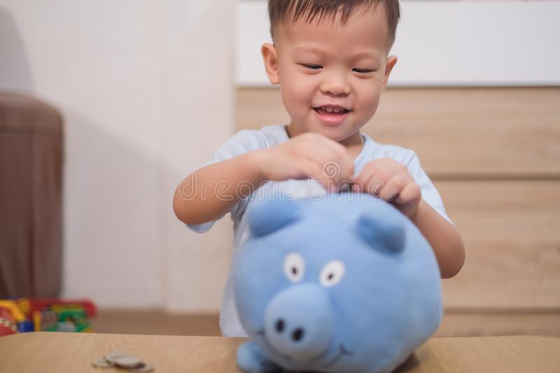 Toddler baby boy child putting Thai coin into blue piggy bank. Cute little Asian 2 - 3 years old toddler baby boy child putting Thai coin into blue piggy bank royalty free stock photography