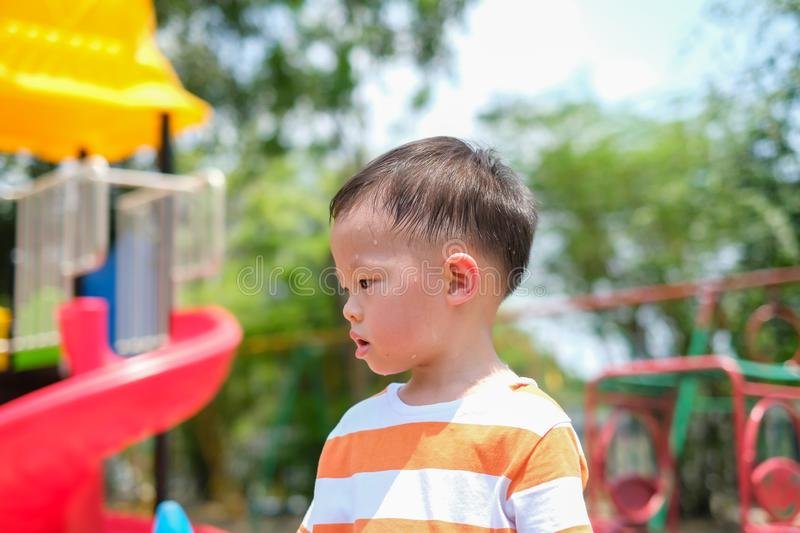 Cute little Asian 2 - 3 years old toddler boy child sweating during having fun playing, exercising outdoor at playground, Heat. Cute little Asian 2 - 3 years old royalty free stock photo