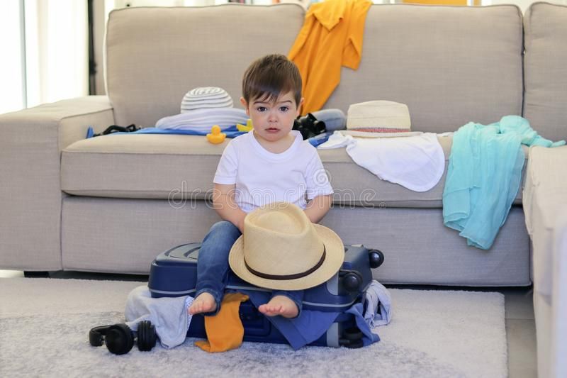 Cute little baby boy with funny face expression holding hat in hands sitting on packed suitcase with clothes sticking out ready to. Leave for vacation royalty free stock image