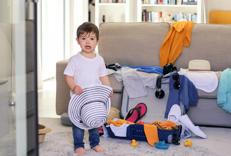 Cute little baby boy with funny surprised face expression holding hat in hands helping to pack suitcase packing clothes and toys f royalty free stock images