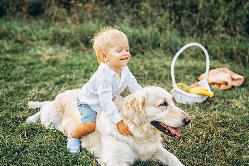 Pretty little baby boy have fun with dog. Cute little baby boy have fun with dog royalty free stock photos