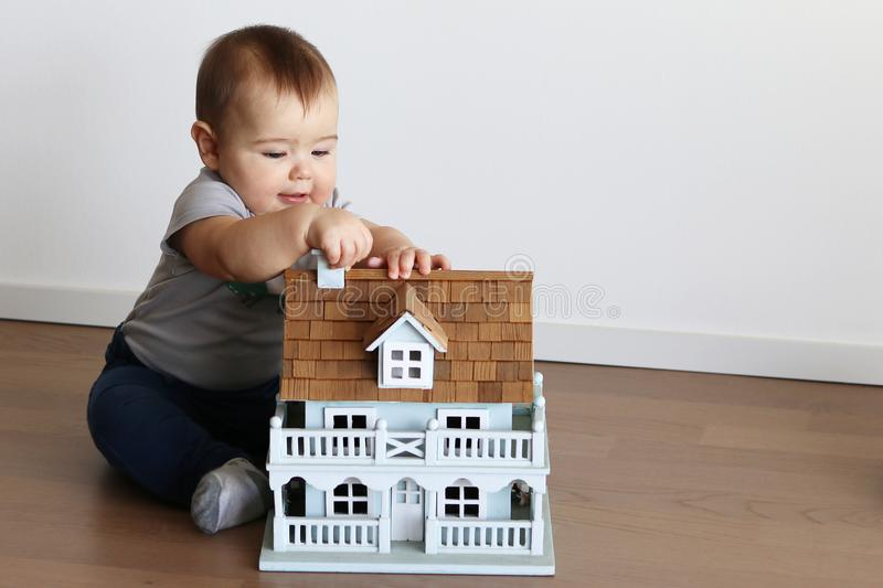 Cute little baby boy playing with small wooden house royalty free stock photos