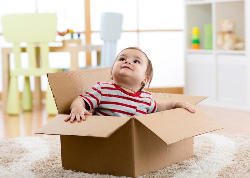 Cute little baby boy sitting inside cardboard box, moving out concept royalty free stock photos