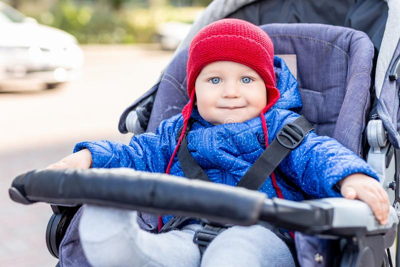 Cute little baby boy sitting in stroller and smiling during walk on cold autumn or winter day.Adorable kid wearing blue jacket and royalty free stock photography
