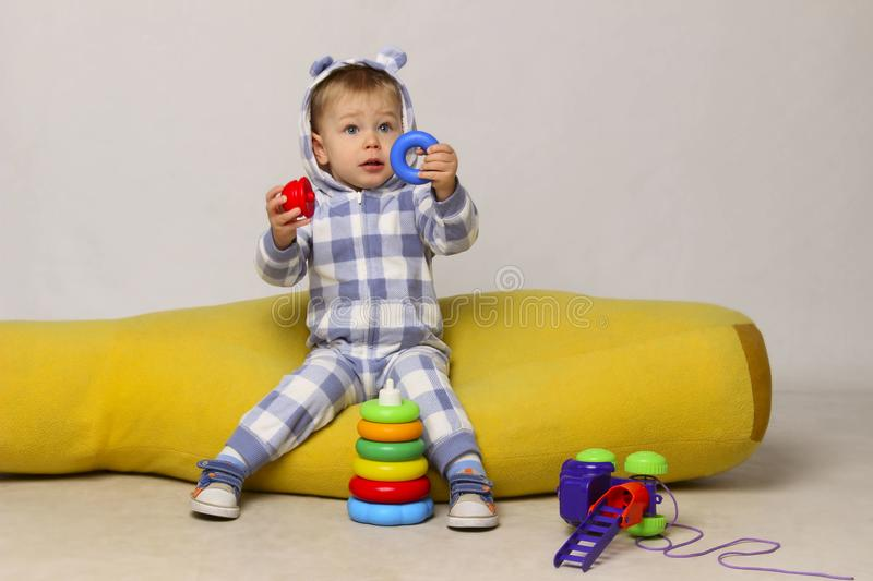Cute Little Baby Boy Sitting On a Yellow Bean Bag Chair and Playing Toys. stock image