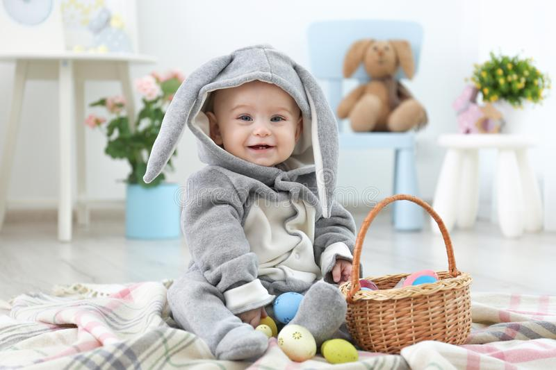 Cute little baby in bunny costume playing with Easter eggs stock photos