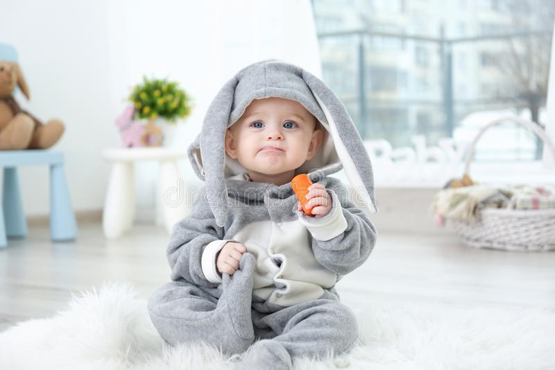Cute little baby in bunny costume sitting on furry rug. And eating carrot stock photos