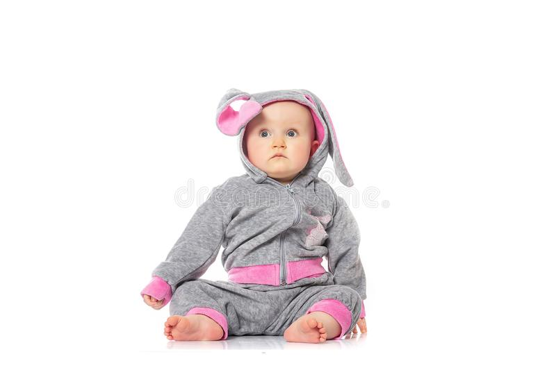 Cute little baby in bunny costume sitting on white background. children`s games. baby emotions stock photo