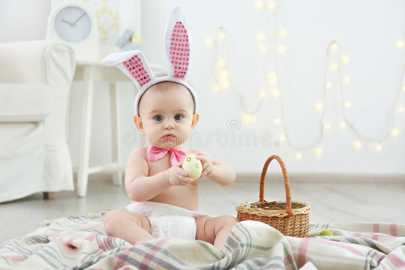 Cute little baby in bunny ears and bow tie playing with Easter eggs stock image