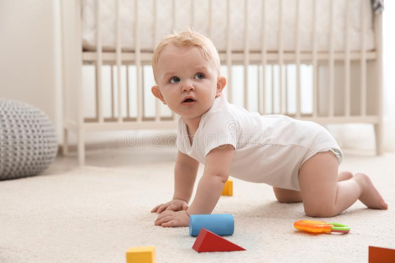 Cute little baby crawling on carpet royalty free stock photo