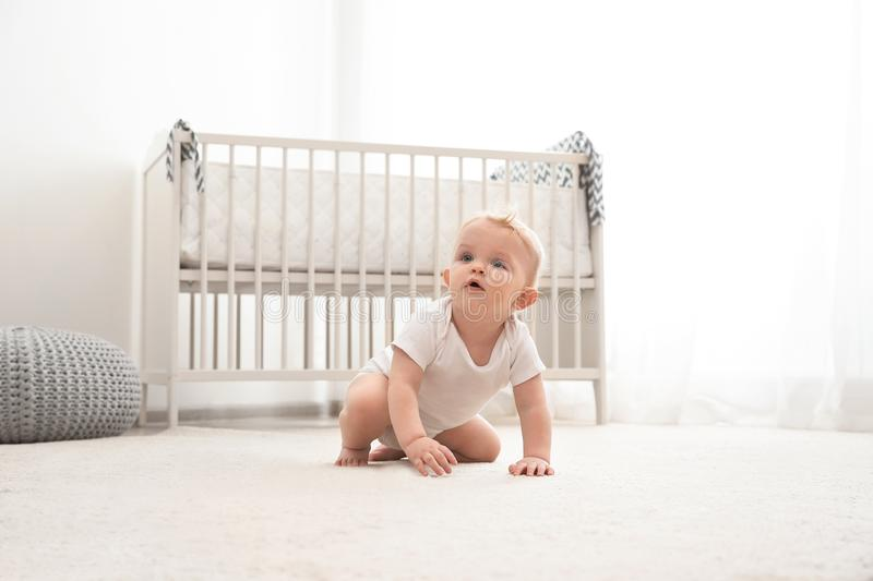 Cute little baby crawling on carpet stock image