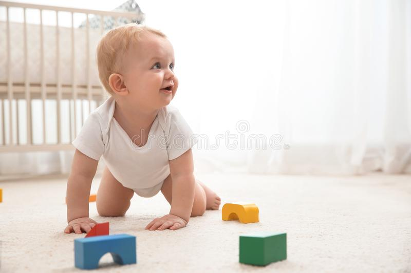 Cute little baby crawling on carpet indoors stock photography