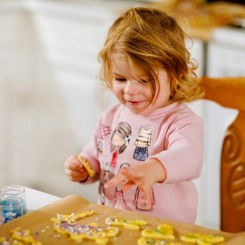 Cute little baby girl baking gingerbread Christmas cookies at home. Adorable blond child having fun in domestic kitchen. Traditional leisure with kids on Xmas stock photo