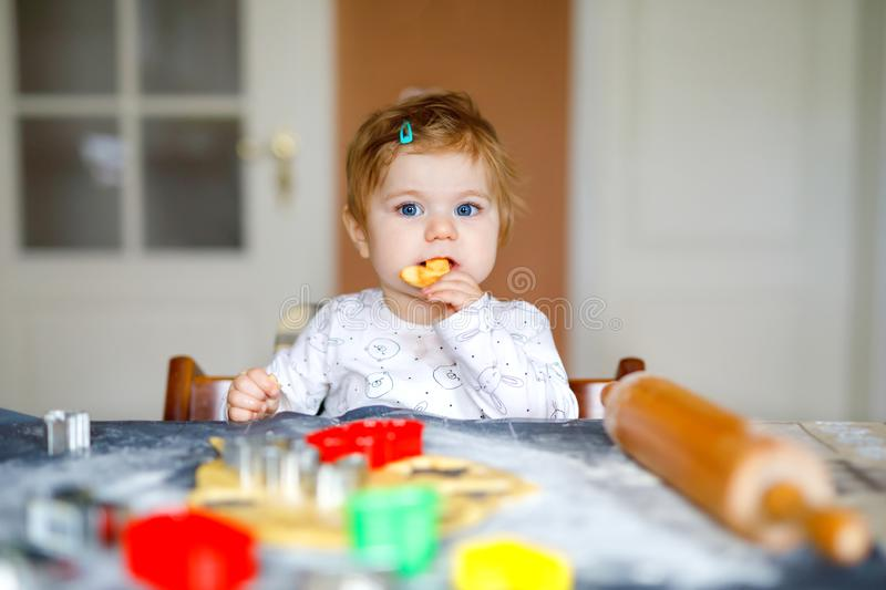 Cute little baby girl baking gingerbread Christmas cookies at home. Adorable blond happy healthy child having fun in royalty free stock images