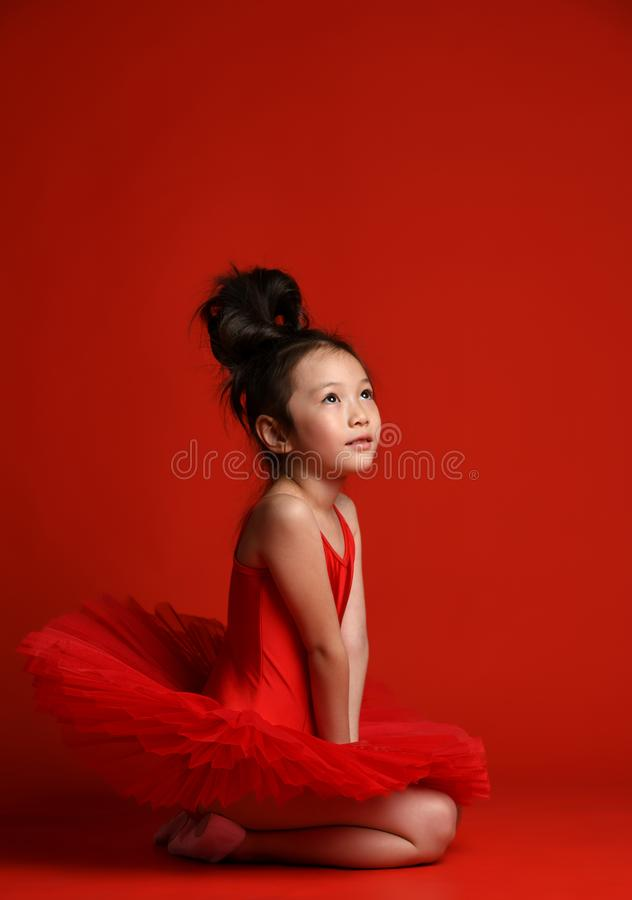Cute little baby girl ballerina in beautiful dress sitting in dancing dress on red royalty free stock photo