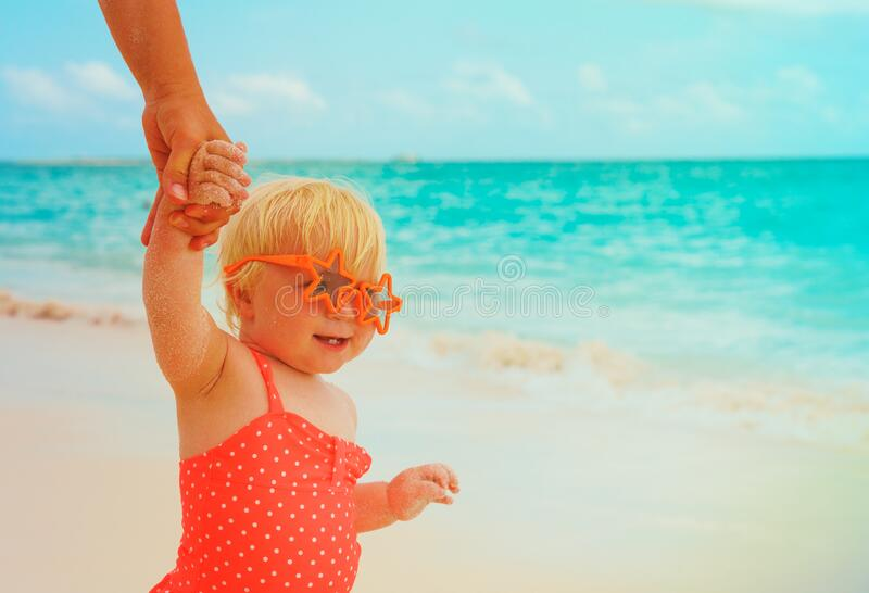 Cute little baby girl on beach holding mother hand, family at beach. Cute little baby girl on beach holding mother hand, family beach vacation royalty free stock photo