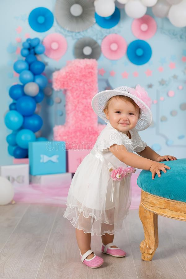 Cute little baby girl with big blue eyes wearing tutu hat and flower in her hair posing sitting in studio decorations with number stock photo