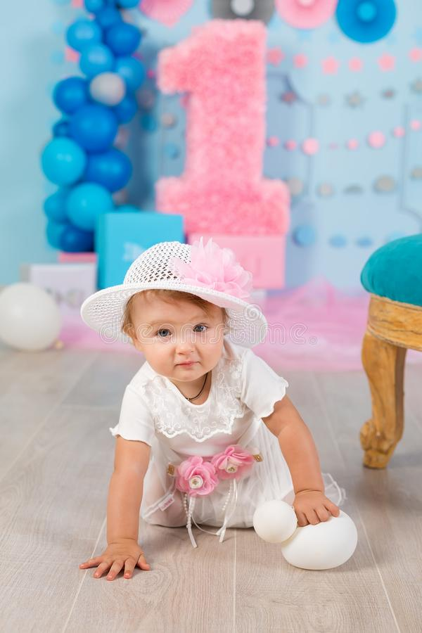 Cute little baby girl with big blue eyes wearing tutu hat and flower in her hair posing sitting in studio decorations with number royalty free stock photo