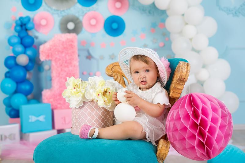Cute little baby girl with big blue eyes wearing tutu hat and flower in her hair posing sitting in studio decorations with number stock photography