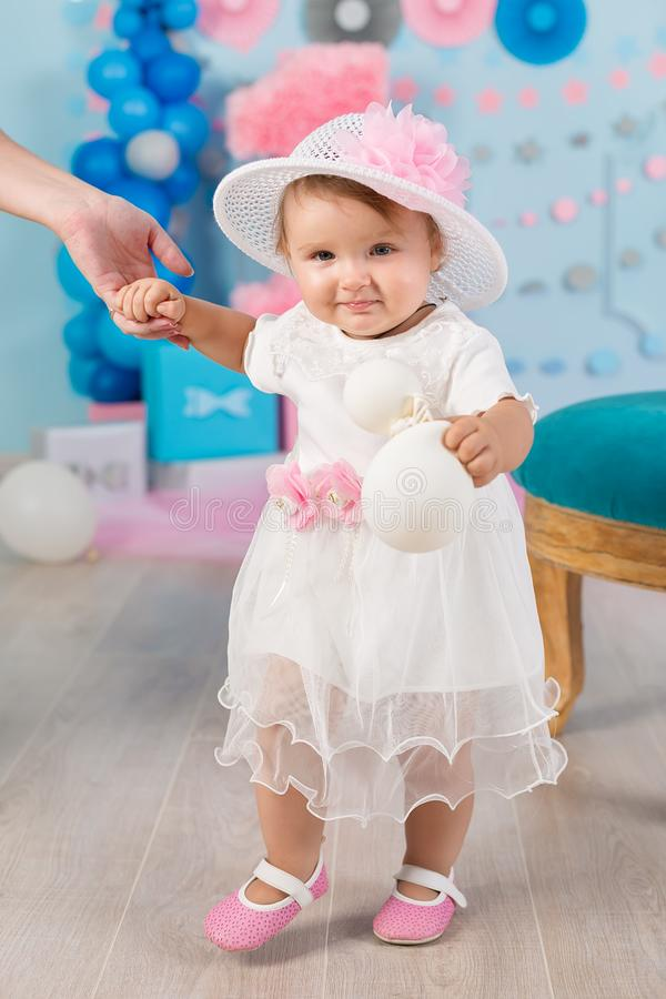 Cute little baby girl with big blue eyes wearing tutu hat and flower in her hair posing sitting in studio decorations with number royalty free stock image