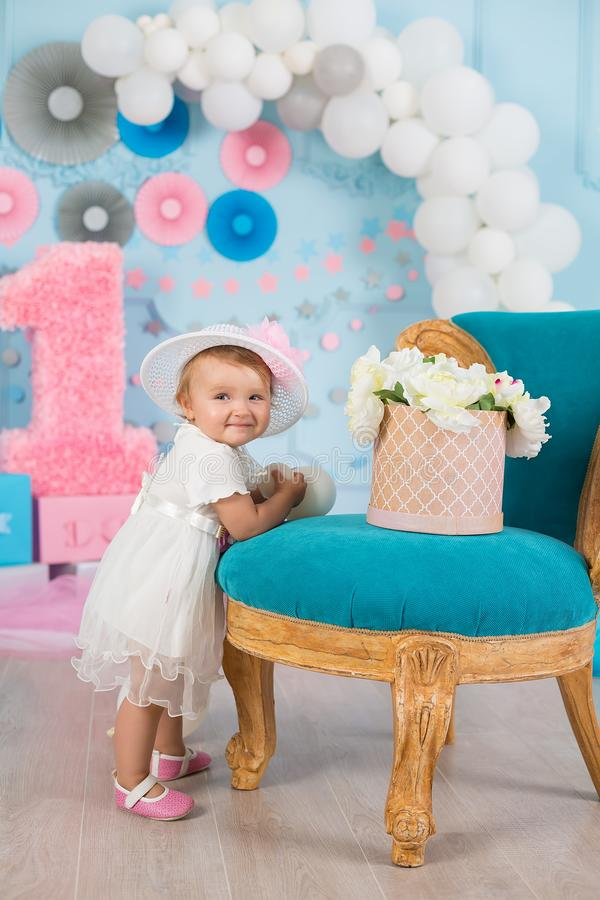Cute little baby girl with big blue eyes wearing tutu hat and flower in her hair posing sitting in studio decorations with number royalty free stock photography