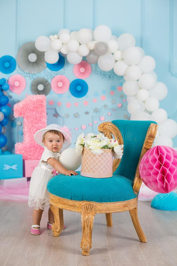 Cute little baby girl with big blue eyes wearing tutu hat and flower in her hair posing sitting in studio decorations with number royalty free stock images