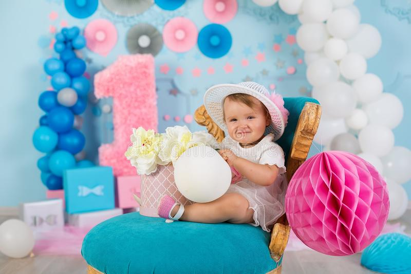 Cute little baby girl with big blue eyes wearing tutu hat and flower in her hair posing sitting in studio decorations with number royalty free stock photos