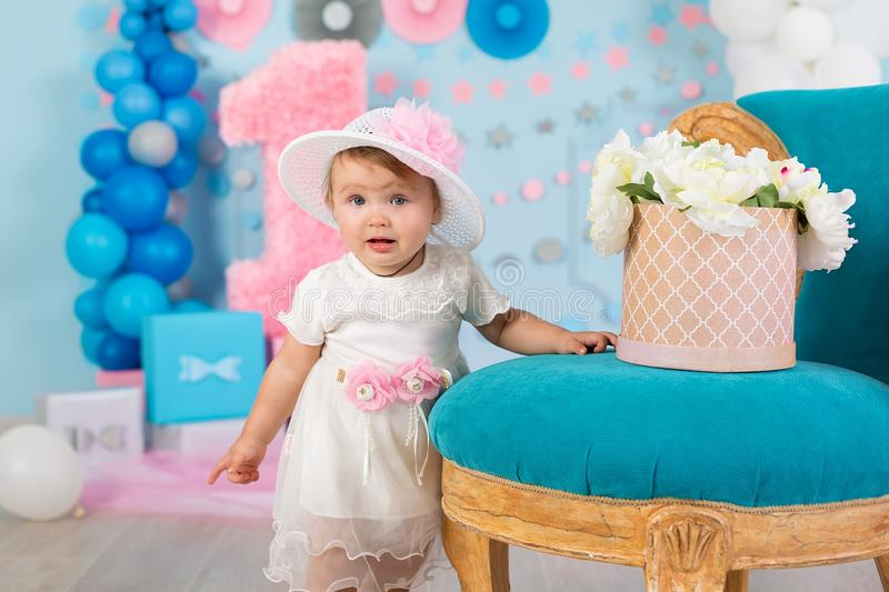 Cute little baby girl with big blue eyes wearing tutu hat and flower in her hair posing sitting in studio decorations with number stock image