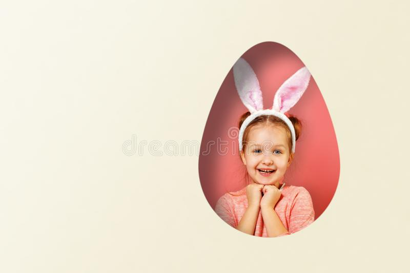 Cute little baby girl with bunny ears. A child in a hole in the shape of an egg on a colored pink and white background. royalty free stock image