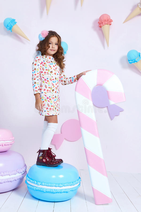 Cute little baby girl fashion pretty model dark blonde curly. Lady hair funny child birthday party fun children room candy bar sweet ice cream play with toy stock image